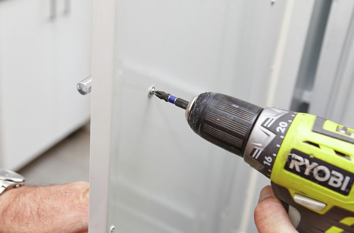 Using the drill to tighten the screws and secure the handle.
