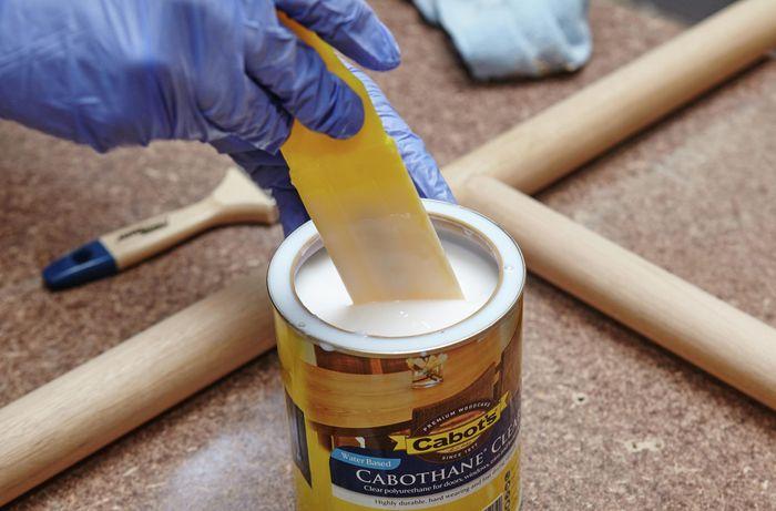 Person dipping brush into tin of varnish.
