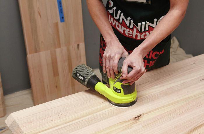 A person sanding a timber panel using an orbital sander