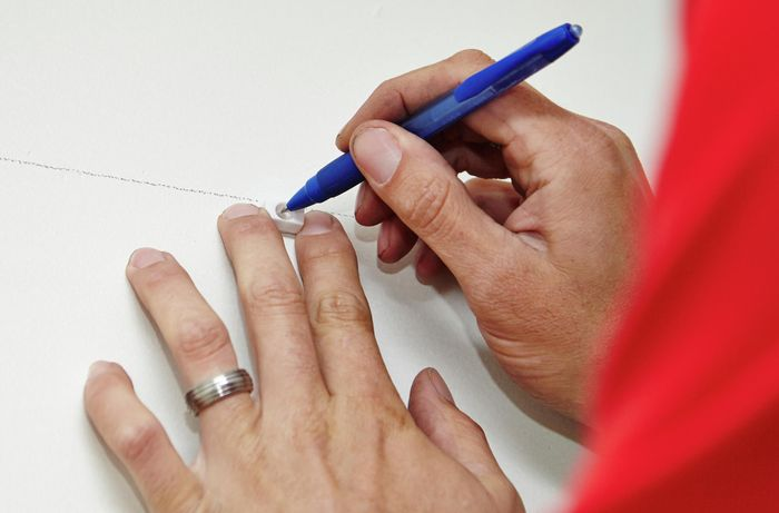 Positions of brackets being marked on a wall with a ballpoint pen by a Binnings team member