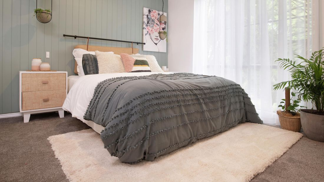 Queen bed with sidetables sitting on a crème rug, in a bedroom with sage feature wall behind it. T