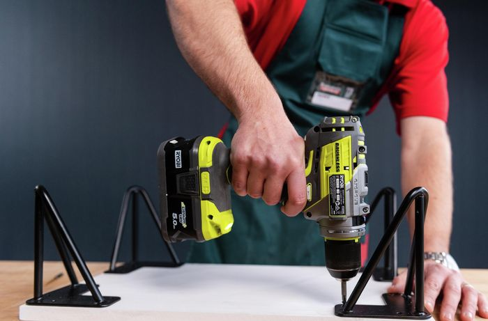 Bunnings team member drilling in hooks with a drill into the timber board