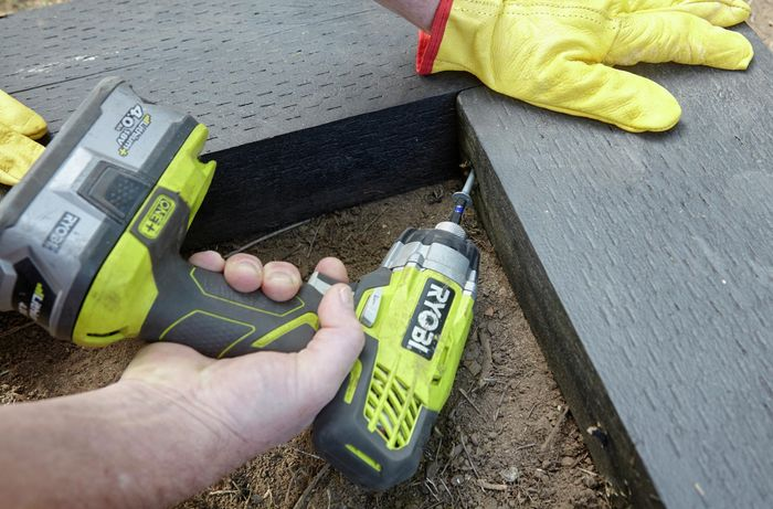 A person joining two sleepers at right angles using a cordless drill