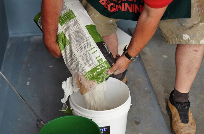 Person pouring powder mastic into bucket.