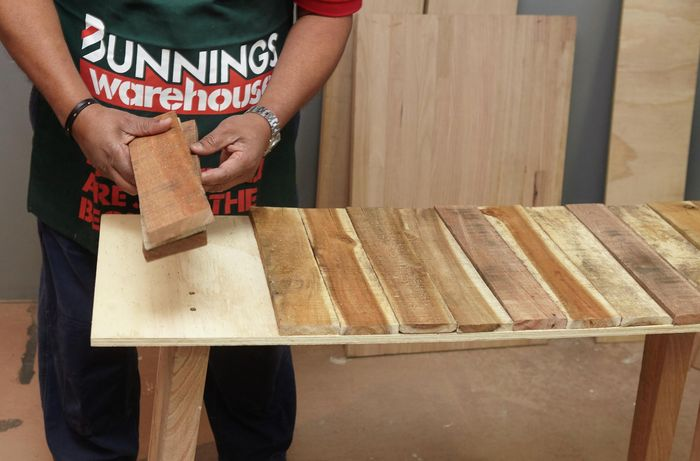 Person laying out timber slats on a workbench