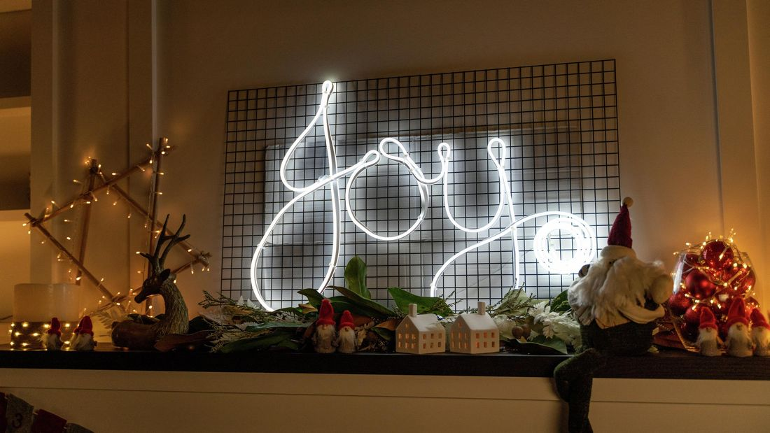 Neon sign which reads 'Joy' sitting on top of a mantel with other Christmas decorations