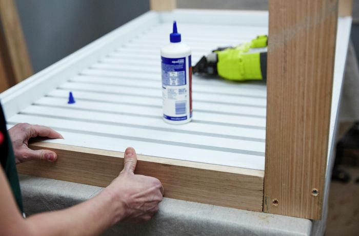 Person attaching trim to edge of coffee table