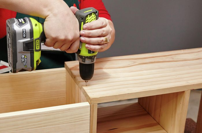 The top bench surface of a wooden storage bench being screwed down by a Bunnings team member