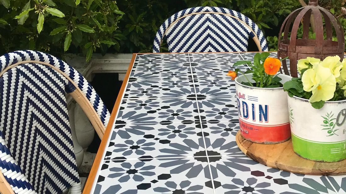 Potted succulent centrepiece on a tiled outdoor dining table