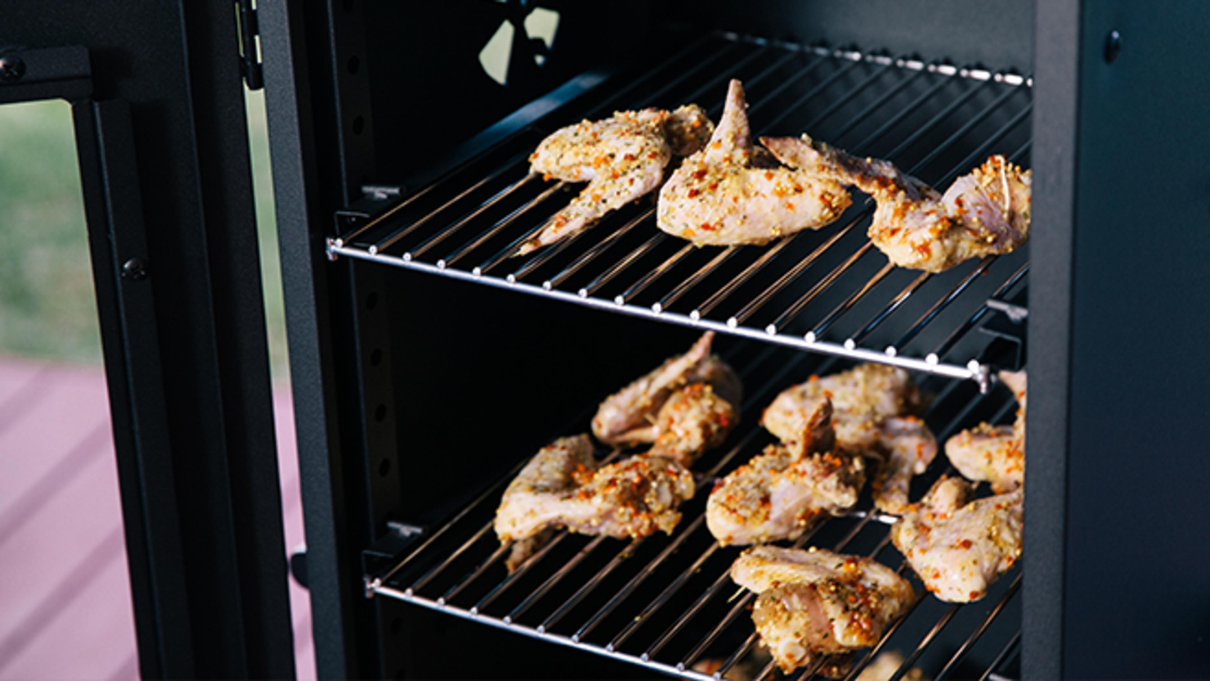 Raw chicken on racks in smoker.