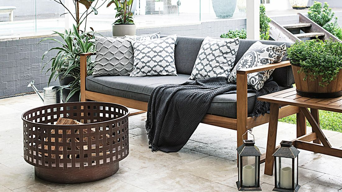 A paved outdoor room with a couch and fire drum