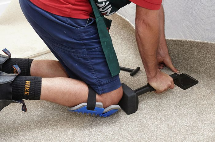 A knee kicker being used to push carpet into the corner of a room