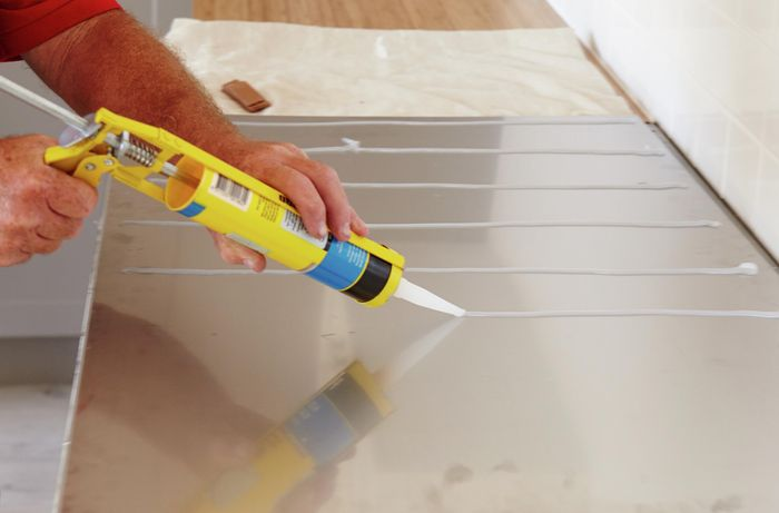Silicone being applied to the back of a stainless steel splashback