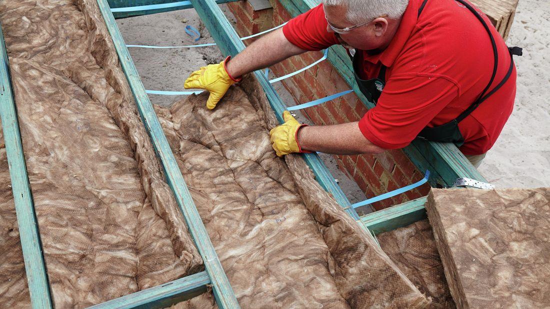A person wearing protective gear placing an insulation batt between floor joists