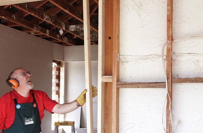 Person installing vertical wall studs between plates.