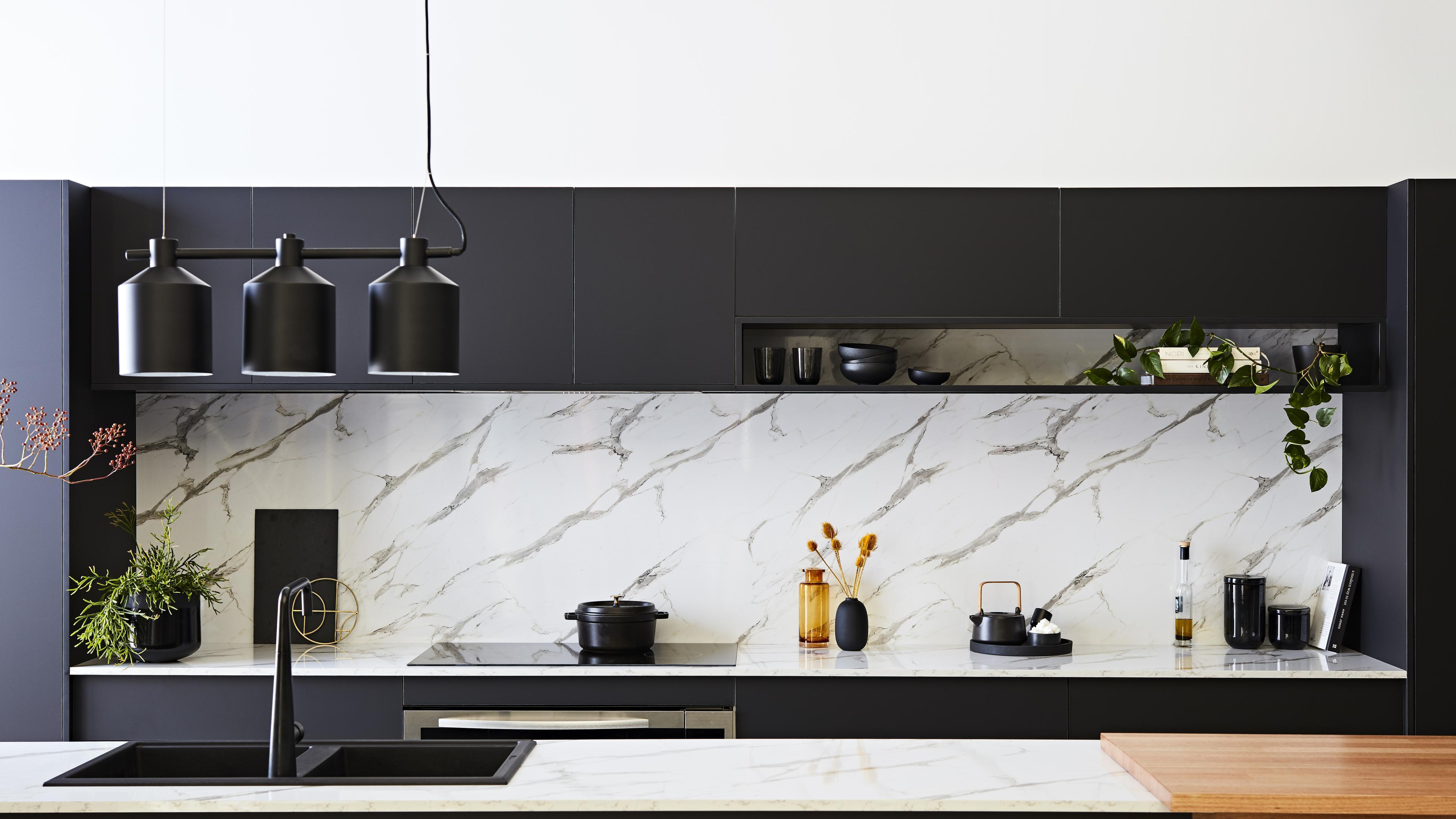 Kitchen with marble splashback and black cabinetry.
