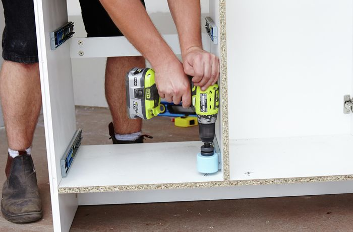 A person using a hole saw attachment to cut holes in the bottom of a bathroom vanity