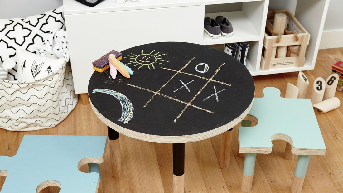 A round chalkboard table with chalk and children's drawings