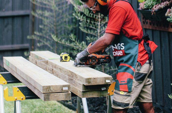 Retaining wall sleepers being cut to size by a Bunnings team member