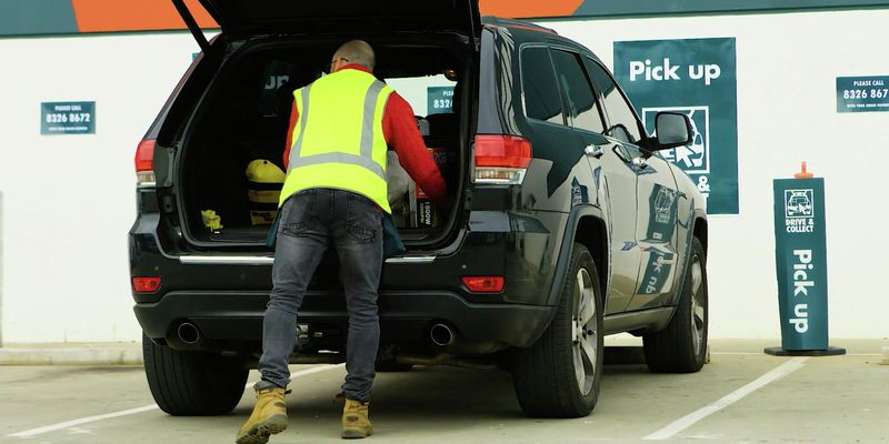 Bunnings Team Member loading goods into a car.