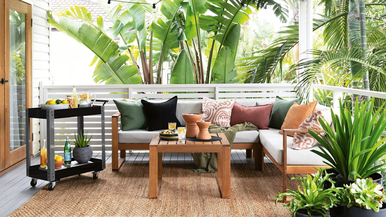 A modern style outdoor lounge retreat on a deck with hanging festoon lights, drinks trolley and potted plants