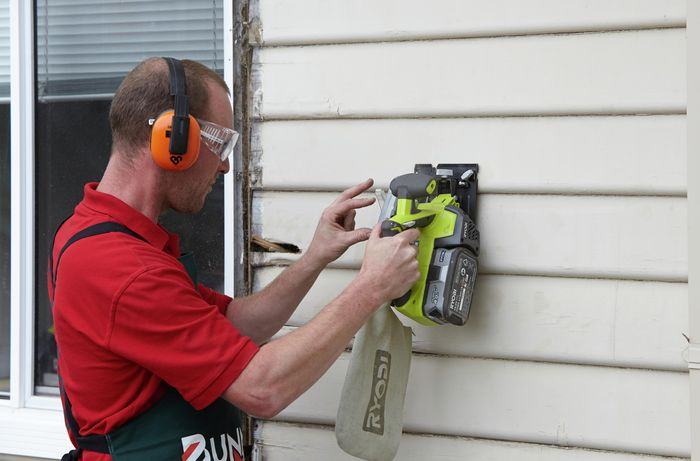 A rotten weatherboard being cut through with a circular saw