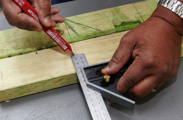 A square rule being used to mark pieces of timber