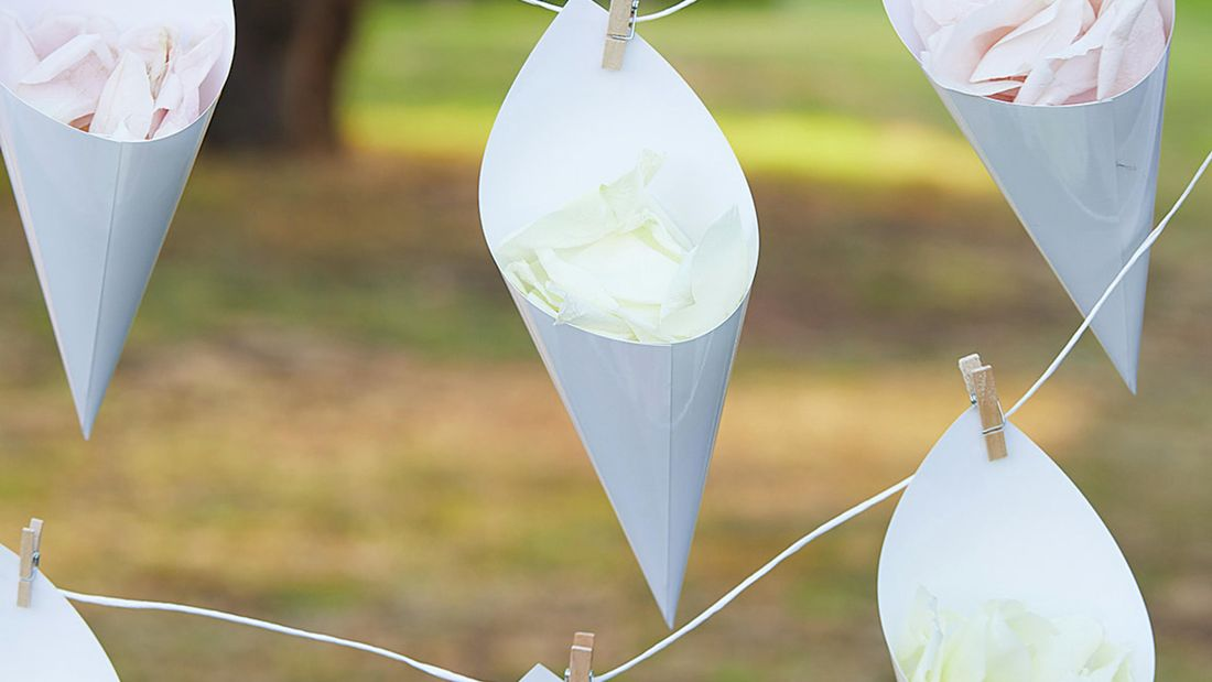 Four decorative cones hang from small pegs filled with rose petals.