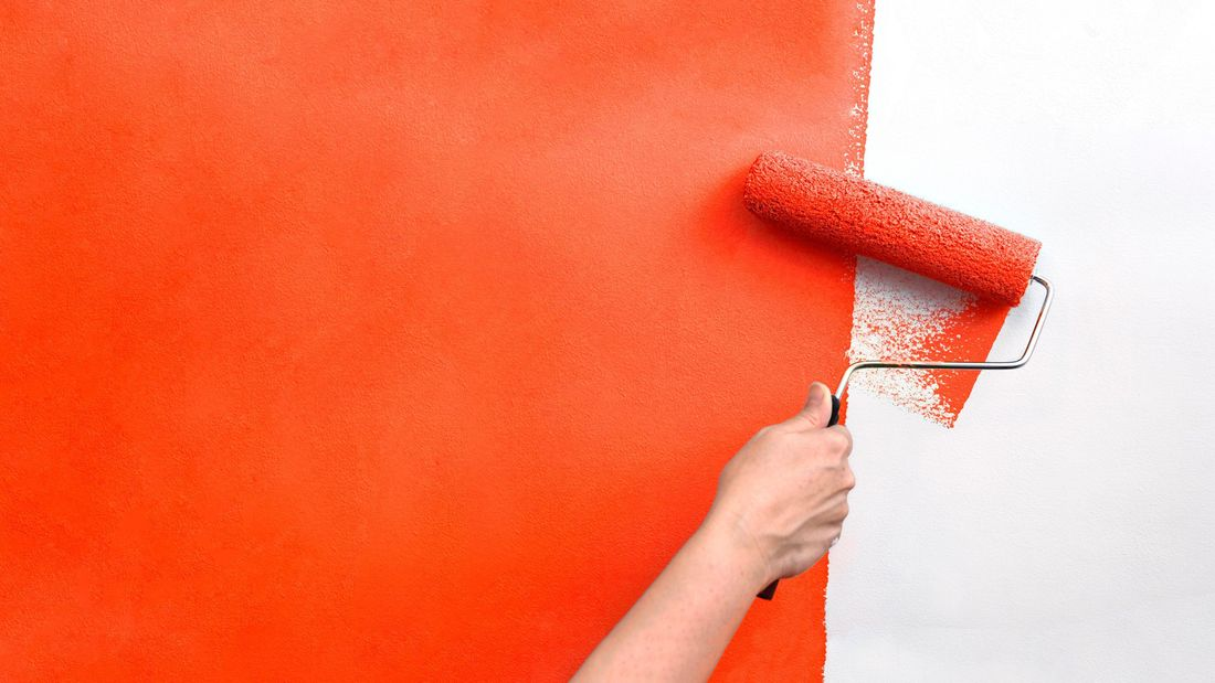A wall being painted orange with a paint roller