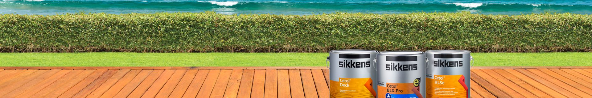 Decking looking out onto ocean, with tins of Sikkens on deck.