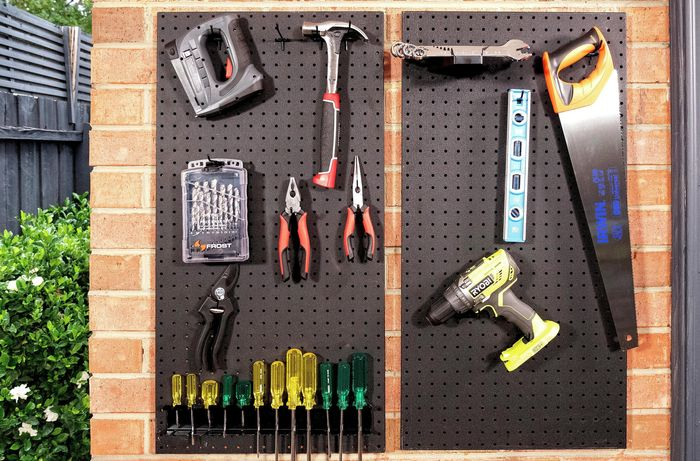 Pegboard with tools hanging off it.