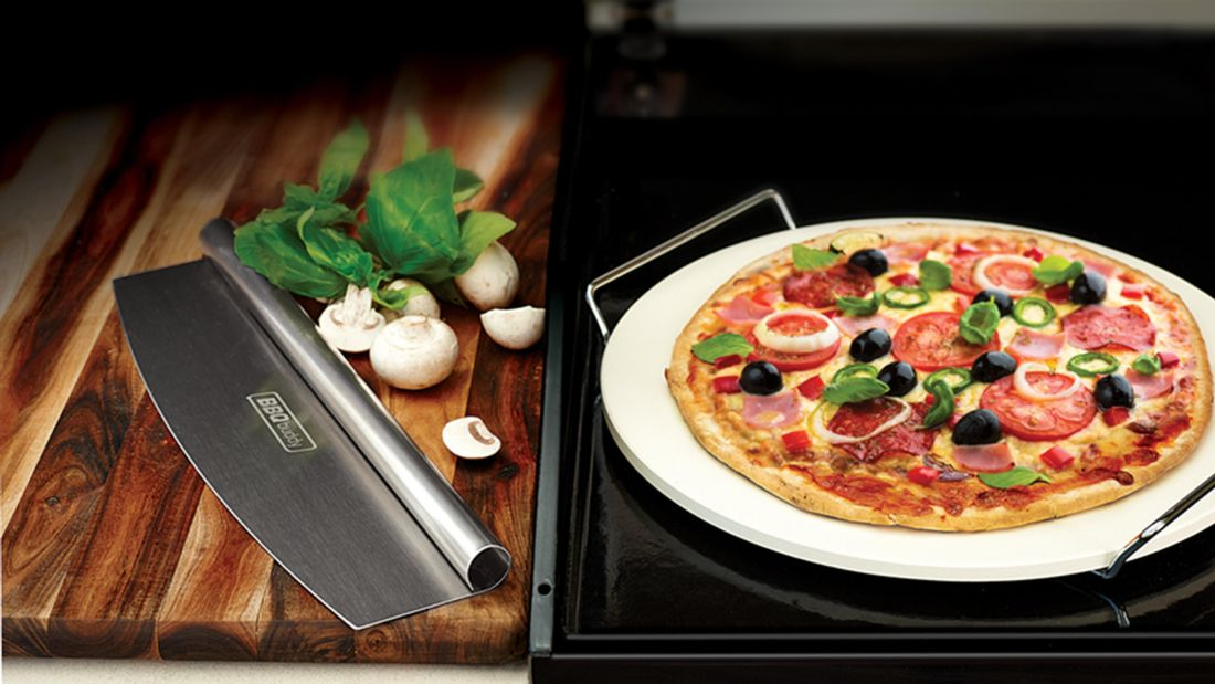 A cooked pizza on a pizza stone, with nearby cutter, herbs and button mushrooms