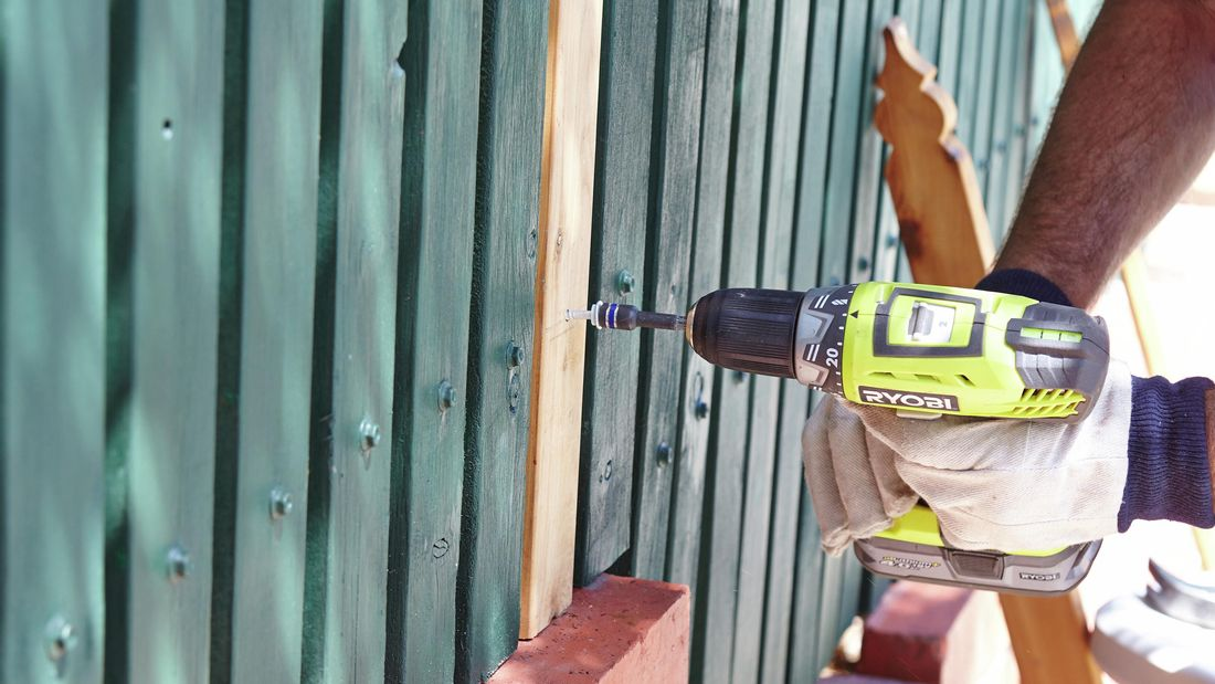 Person drilling pickets in picket fence.