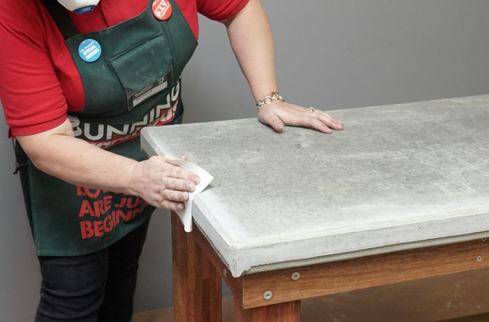 Person wiping concrete table benchtop with cloth.