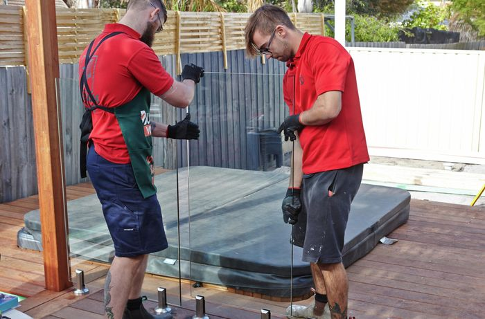Two people putting glass pool fencing panel in place.