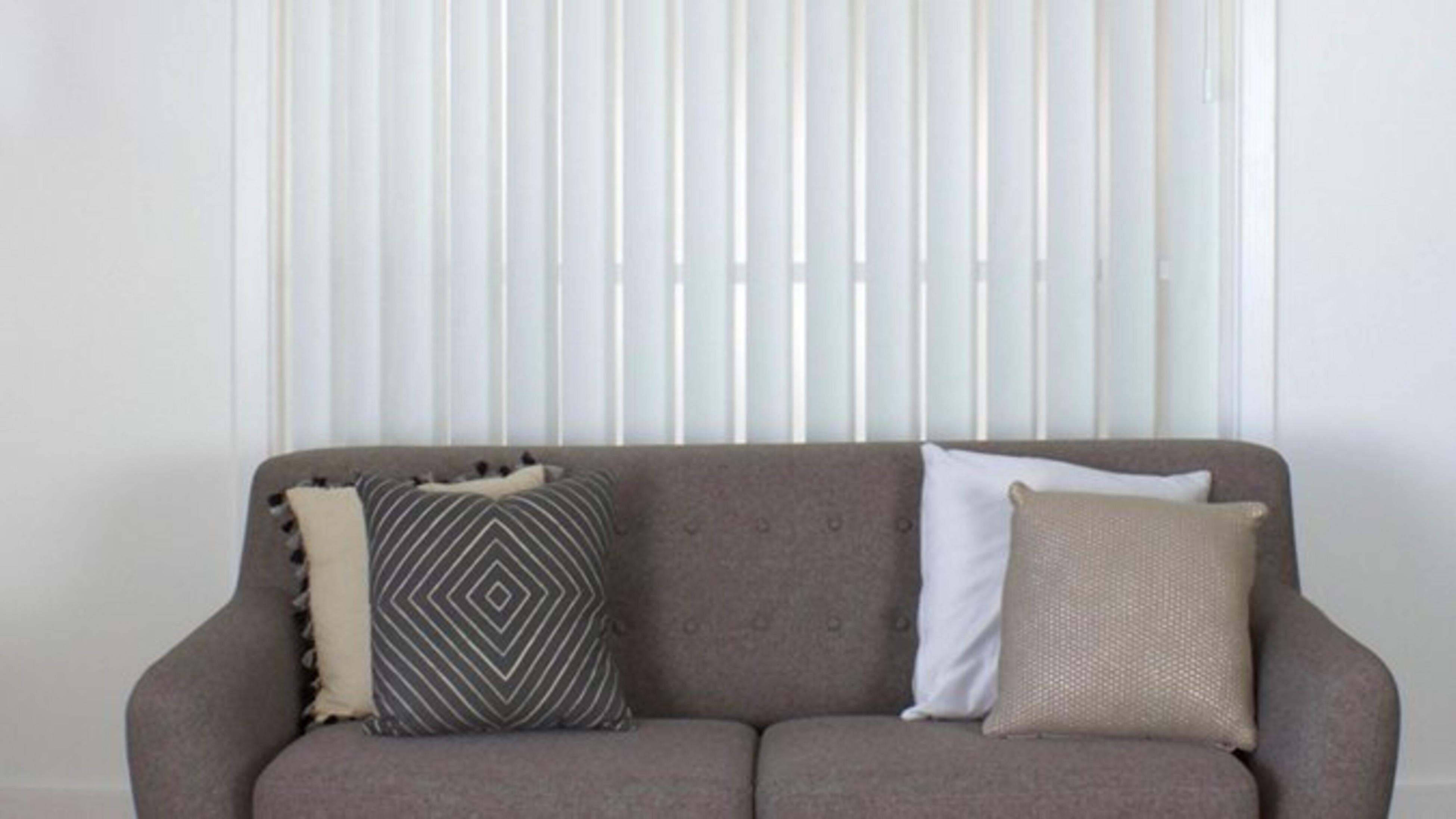 White vertical blinds behind a grey couch with cushions.