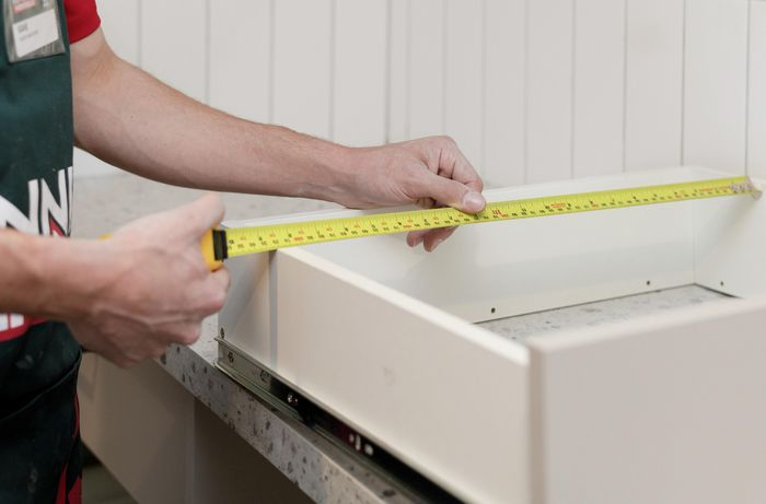 Measuring drawers with a tape measure.