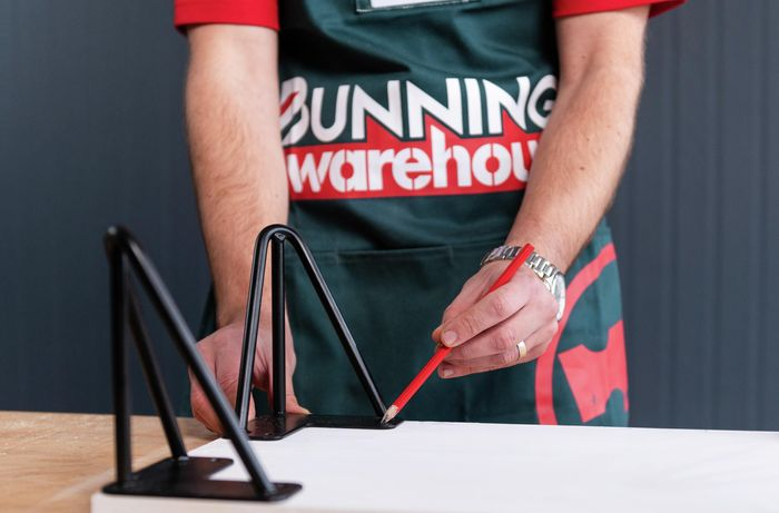 Bunnings team member marking out where the screws will go with a pencil on the timber board
