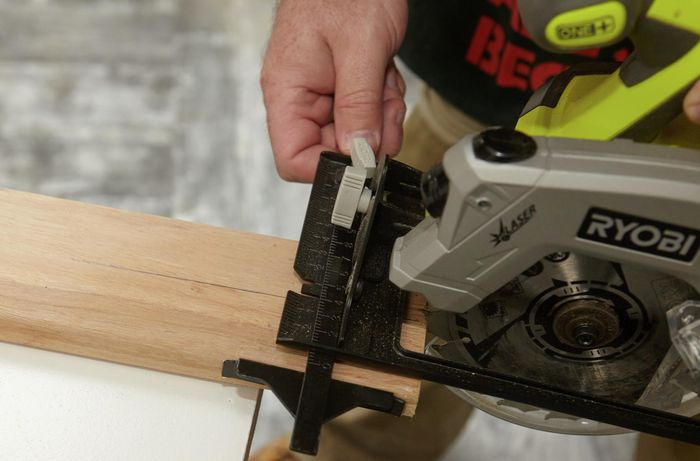 A person cutting a piece of timber lengthwise using a circular saw