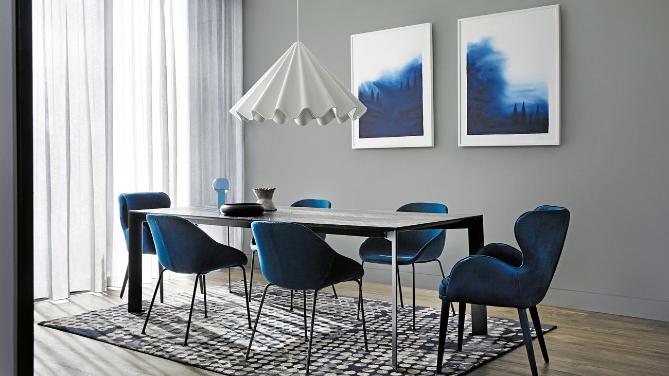 Dining room with blue velvet chairs and industrial table with a white hanging pendant and two large prints on wall
