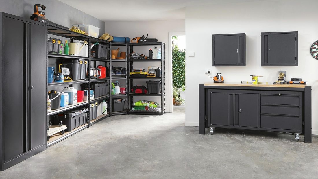 A neatly organised workshop with steel cabinets and shelving, a wooden benchtop and a lockable steel cabinet on wheels