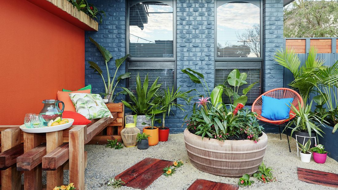 Outdoor area with blue walls and furniture, plants.