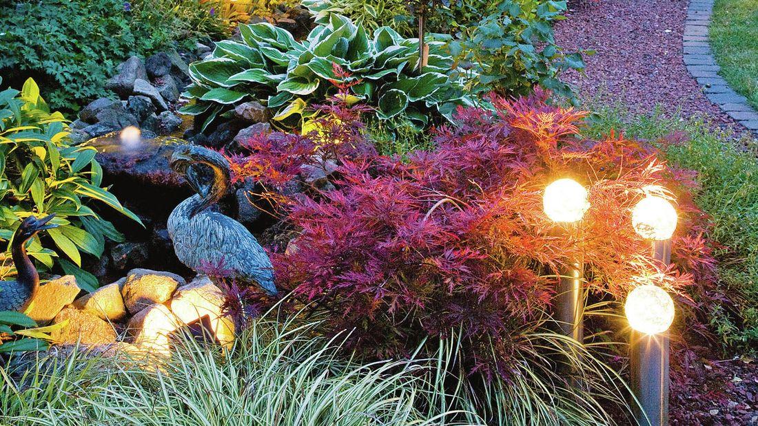 Garden lighting in an outdoor garden setting with decorative birds.