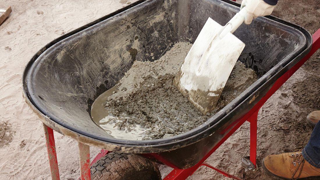 Concrete being mixed in a wheelbarrow with a shovel