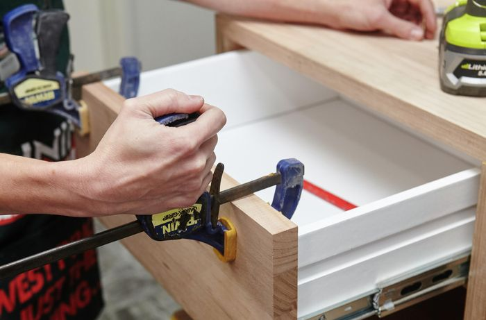 A person clamping a piece of timber to the front of a drawer