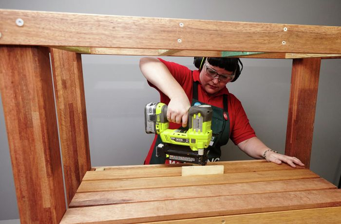 Person drilling slats to create bottom shelf of DIY kitchen island table.