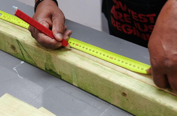 A pencil and tape measure being used to mark a length of wood