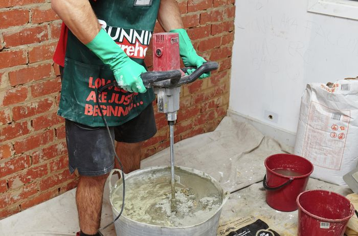 A person mixing cement plaster mix in a bucket using an electric mixer