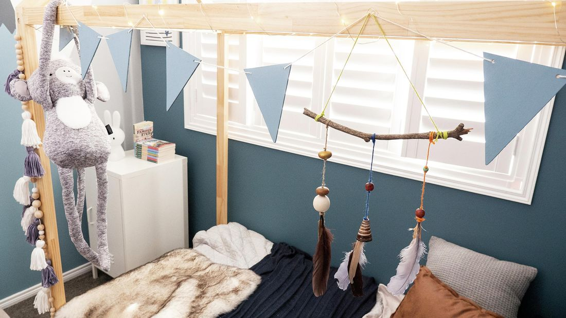 A nature hanging with sticks, beads and feathers, and a bunting hanging over a child's bed.