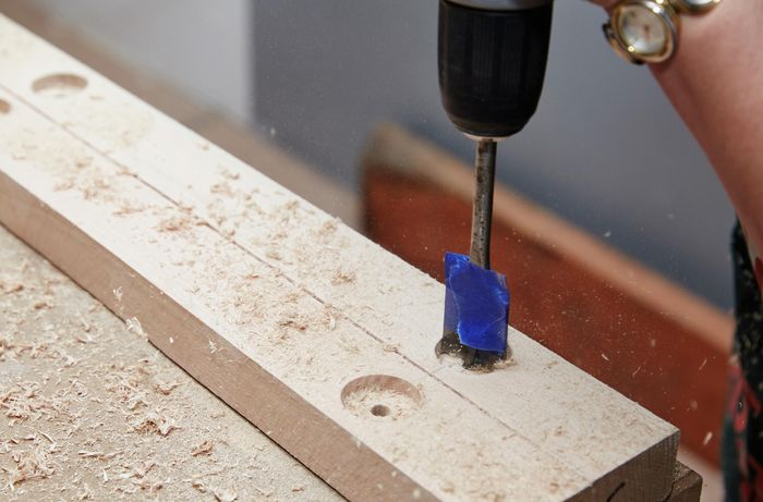 Person using drill with wide drill bit to create a hole in a piece of timber.